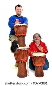 a couple with down syndrome playing on djembe