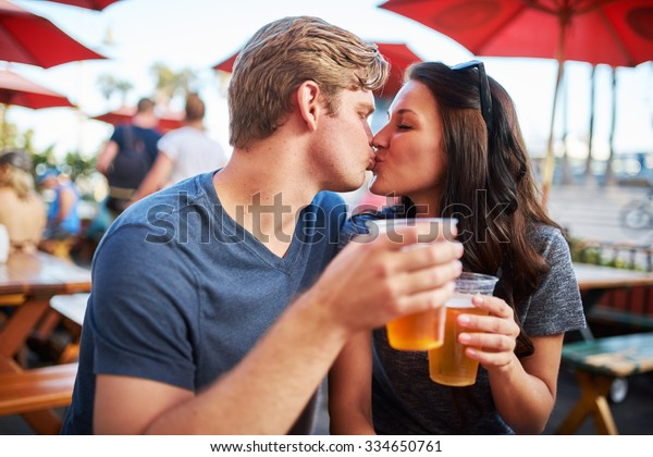 couple with draft beers kissing at outdoor pub or bar patio shot with selective focus