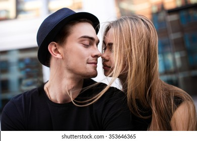 Couple dressed in black looking at each other, the guy wear black hat, a girl flying hair, close-up portrait