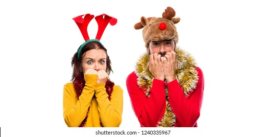 Couple dressed up for the christmas holidays is a little bit nervous and scared putting hands to mouth on isolated background