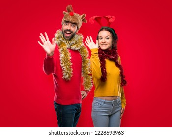 Couple dressed up for the christmas holidays saluting with hand with happy expression on isolated red background