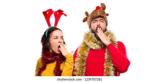 Couple dressed up for the christmas holidays yawning and covering mouth with hand. Sleepy expression on isolated background