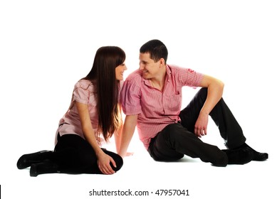 Couple dressed in pink clothes isolated on white sitting and look each others