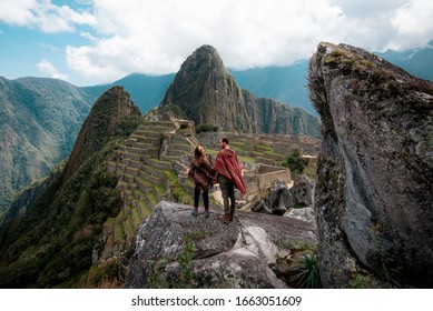 Couple dressed in ponchos watching the ruins of Machu Picchu - Shutterstock ID 1663051609