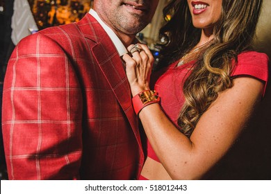 Couple dressed in red suits hugs each other