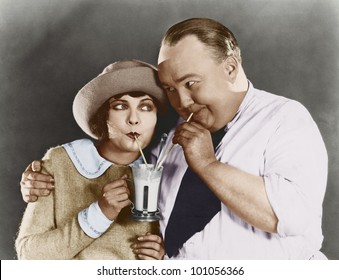 Couple drinking beverage with straw
