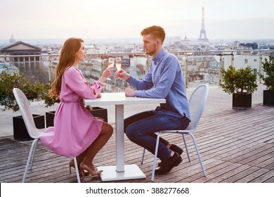 couple drinking champagne in luxury rooftop restaurant in Paris with panoramic view of Eiffel Tower