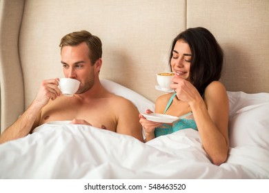 Couple drinking coffee in bed. Woman smiling and holding cup. Warm Sunday morning at home.
