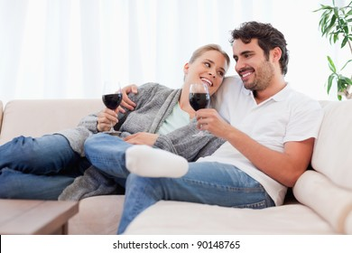 Couple drinking a glass of  red wine in their living room