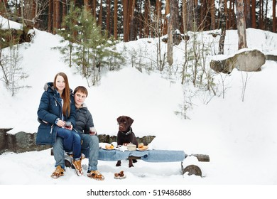 Couple drinking hot drink outdoors in rural winter weekend