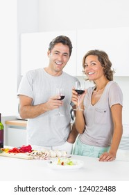 Couple drinking red wine and preparing salad in the kitchen