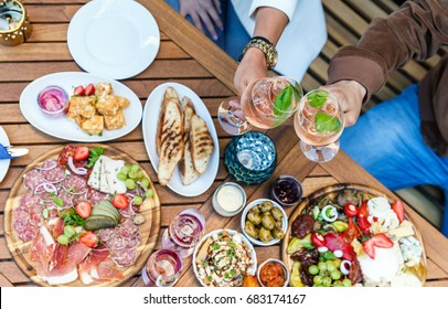 Couple drinking white and rose wine while having a delicious dinner with lots of appetizers