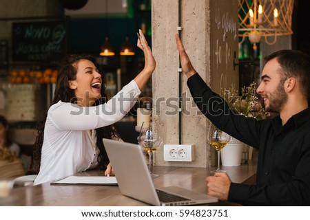 Couple drinking wine and having fun, high five