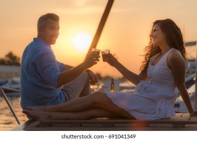 Couple drinking wine on a boat int he sunset in the marina