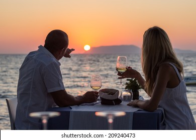 Couple drinking wine at sea beach restaurant at sunset