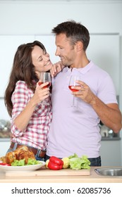 Couple drinking wine while fixing dinner