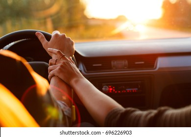 The couple drives the car on the way to the sunset. He drives the car, she holds his hand. Shooting close-up. Go to the sunset. Travel of lovers.