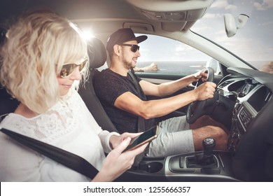 Couple driving in a car next to the ocean