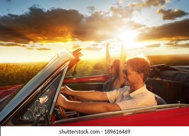 Couple driving convertible car enjoying a summer day at sunset