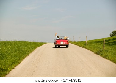 Couple driving convertible in countryside