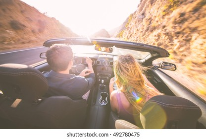 Couple driving fast on a sport convertible car in the canyons. Romantic road trip