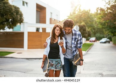 Couple driving a long board and looking at a mobile phone.