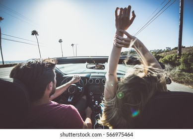 Couple driving on a convertible car