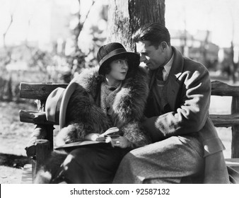 Couple in each others arms sitting on a park bench