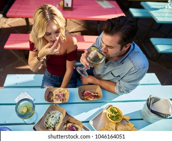 couple eating authentic street tacos at outdoor mexican restaurant