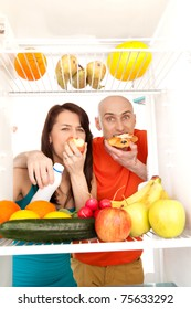 A couple eating cream cakes standing in the open door of the refrigerator full of healthy fresh fruit.