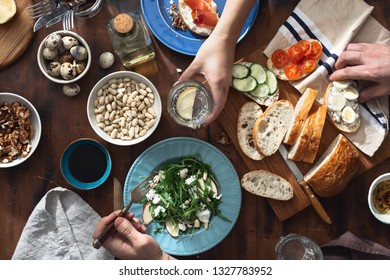 Couple eating delicious and healthy breakfast or lunch top view. Various snacks, appetizers, arugula salad, sandwiches with prosciutto and vegetables