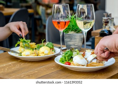 A couple eating a lunch of the Benedict eggs
