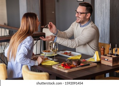 Couple eating lunch at a restaurant, tasting each other's food and having fun
