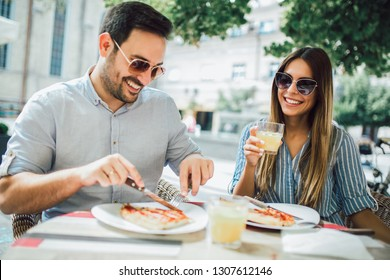 Couple eating pizza snack outdoors.They are sharing pizza and eating.