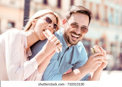 Couple eating sandwiches on a sunny summer day in the park after shopping.