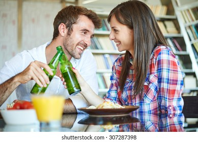 Couple eating spaghetti in home, cheers with beer bottle