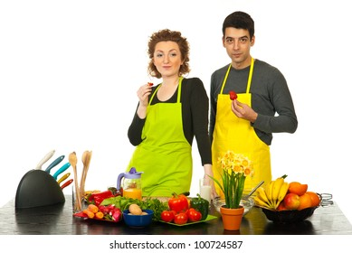 Couple eating strawberries in their kitchen and making a break from cooking against white background