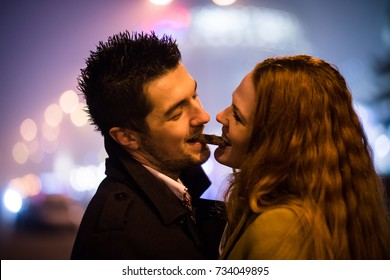 Couple eating together one piece of chocolate in street at night
