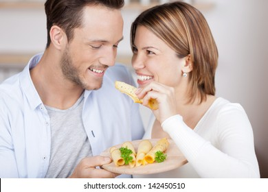 Couple eats some cheese from a variety on plate