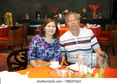 couple elderly people eating chili with red table. Man and woman in Chinese restaurant in new year festival event with happy retried life.