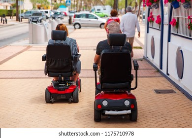 Couple elderly people ride along the sidewalk to an electric wheelchair. Motorized wheelchair. Mobile scooter.