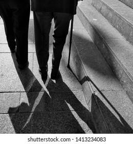 A couple of elderly people walking on a city street