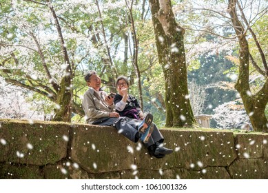 Couple of elderly travel in japan sit and having happy time during spring season in cherry blossom park
