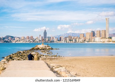 Couple eldery people sitting against sea and watching at Benidorm city