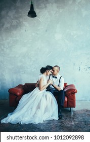 couple embrace on a background of textured walls in the loft, the bride in a wedding dress groom in trousers and a white shirt with suspenders