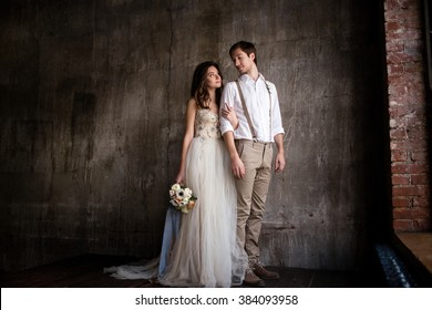 couple embrace on a background of textured walls in the loft, the bride in a wedding dress and beige with a bouquet of anemones in hand, groom in beige trousers and a white shirt with suspenders