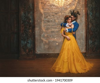 Couple embrace in room old castle. beauty and beast Happy woman fantasy princess in yellow dress guy is enchanted prince, horns on head. Romantic male hugs girl in arms. Man monster carnival costume