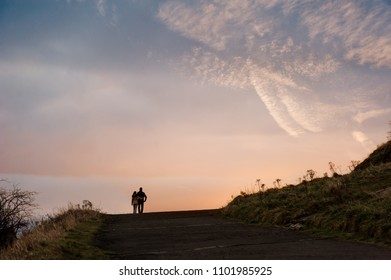 A couple embraced as they walk along a path at sunset.