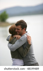 Couple embracing each other by a lake