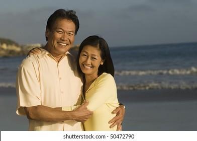 Couple embracing on beach, (portrait)